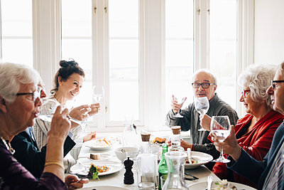 Senior friends with wineglass toasting in restaurant - p426m2149138 by Maskot