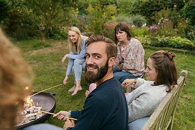 Roasting campfire bread - p788m2037427 by Lisa Krechting