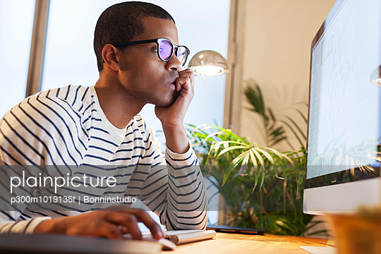 Young creative man working at computer in his home office - p300m1019135f by Bonninstudio