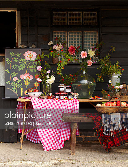 Table laden with harvest produce: Dahlia and rosehip and hawthorn berries  apples plums and jams - p349m2167890 by Sussie Bell