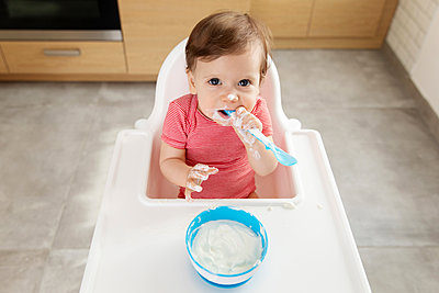 Baby in high chair eating yogurt with spoon - p1166m2084908 by Cavan Images