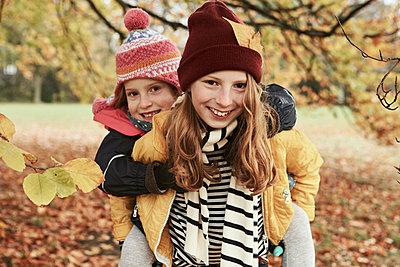 Mädchen reitet Huckepack bei ihrer Schwester - p1344m1208780 von petitepomme
