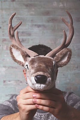 Young man holding artificial deer head  in front of his face - p300m1189281 by Retales Botijero