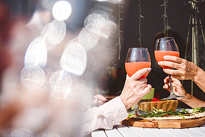 Female friends toasting drinks while sitting at restaurant - p300m2226622 by Katharina und Ekaterina