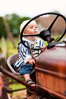 Portrait of baby boy on tractor - p312m695634 by Peter Rutherhagen