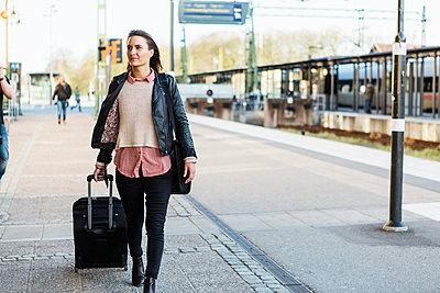 Businesswoman pulling wheeled luggage while walking on railroad station platform - p426m1085546f by Kentaroo Tryman