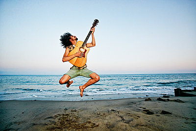 Mixed Race man playing guitar and jumping at beach - p555m1301728 by Peathegee Inc