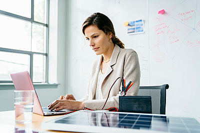 Businesswoman using laptop computer while sitting against whiteboard in office - p1166m1474620 by Cavan Images