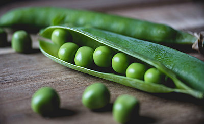 Close-up of green peas on table - p1166m1546365 by Cavan Social
