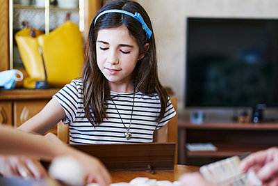 girl playing board games at home - p1166m2201393 by Cavan Images