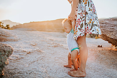 Mom helping baby boy walk on rocks at sunset - p1166m2201923 by Cavan Images