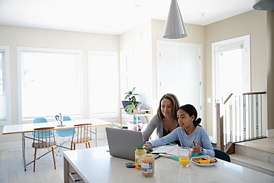 Mother helping daughter with homework at laptop in kitchen - p1192m2094341 by Hero Images