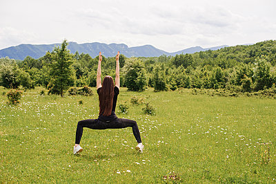 Girl practicing yoga on the mountain plain - p1412m2100830 by Svetlana Shemeleva