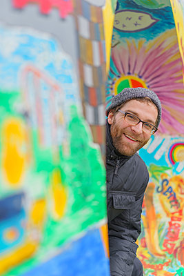 Portrait of smiling young man with graffiti - p300m2080784 by Albrecht Weißer