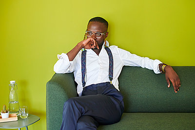 Thoughtful young man wearing fancy glassses sitting on green couch - p300m2143813 by Ivan Gener