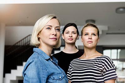 Portrait of confident young businesswomen in office looking away - p300m2166273 by Buero Monaco