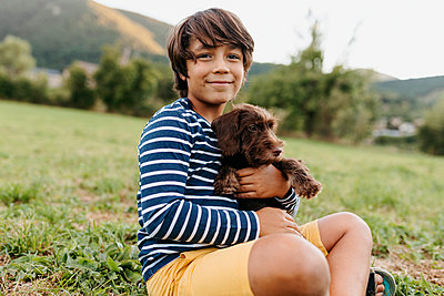 Boy holding puppy while sitting on grass at backyard - p300m2221321 by Valentina Barreto