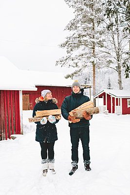 Finland, Jyvaskyla, Saakoski, Young couple standing and holding firewood with houses in background - p352m1141627 by Eija Huhtikorpi