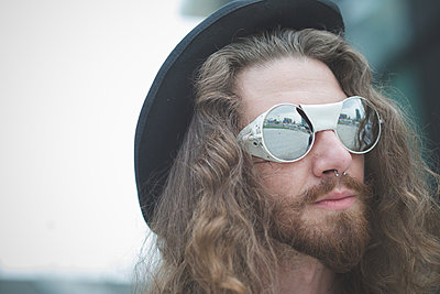 Close up of young male hippy with long hair and sunglasses - p429m1013871f by Eugenio Marongiu