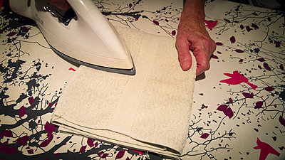 Close-up of a woman's hand ironing a towel. - p813m1488199 by B.Jaubert