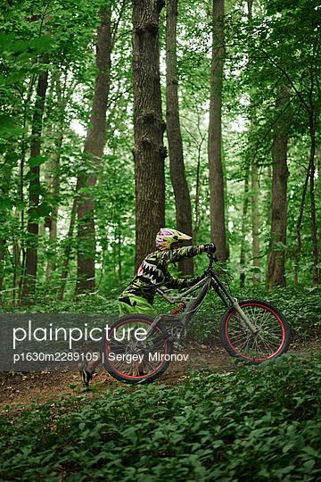 Mountainbiker pushing mountainbike uphill - p1630m2289105 by Sergey Mironov