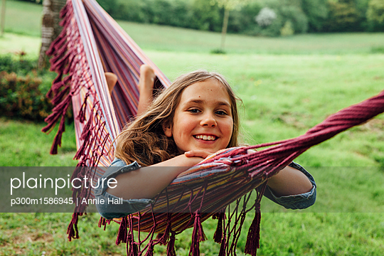 Portrait of happy girl lying in hammock - p300m1586945 von Annie Hall