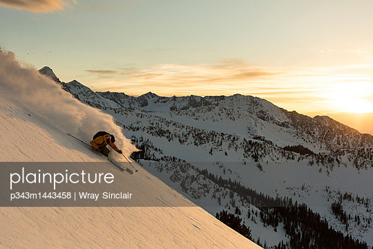 Extreme skier skiing down slope at sunset