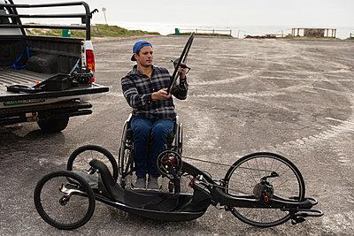 Disabled man in a wheelchair assembling a bike - p1315m2131525 by Wavebreak