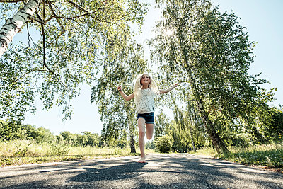 Happy girl skipping rope on a park path - p300m2160735 by Wilfried Feder