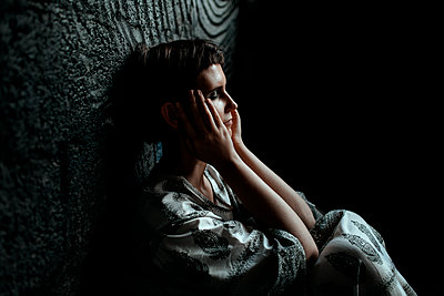 Russia, Moscow, Tired woman with eyes closed and head in hands sitting by wall - p300m2199403 by Oxana Guryava