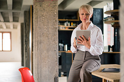 Smiling female entrepreneur using digital tablet while sitting on desk at in home office - p300m2267799 by Robijn Page