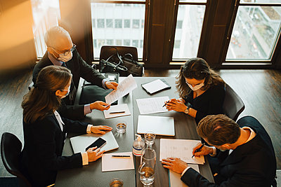 High angle view of business people writing on paper during meeting at board room in office - p426m2270857 by Maskot