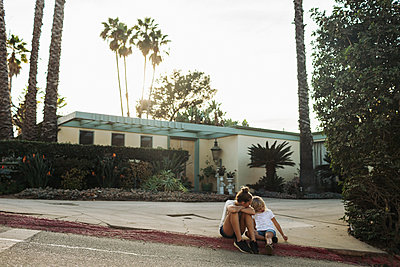 Two young girls sit on a street curb outside a house; Los Angeles, California, United States of America - p442m2016334 by Melody Davis