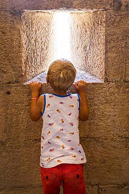 Boy looking through arrow slit - p756m2056894 by Bénédicte Lassalle