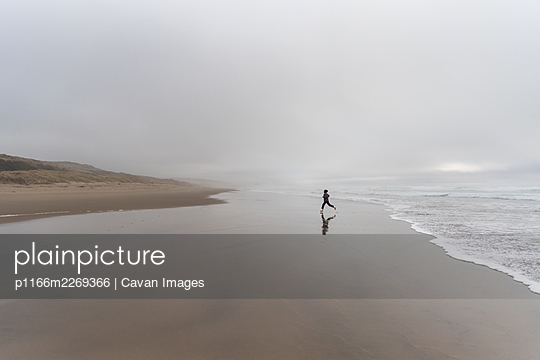 One person striding away from edge of ocean waves on overcast day - p1166m2269366 by Cavan Images