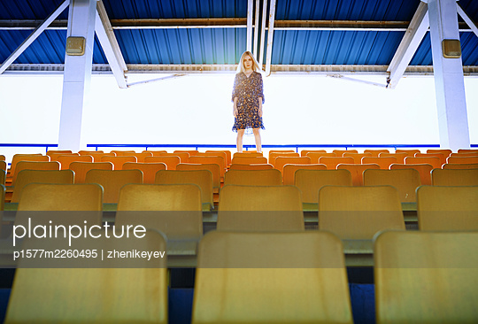 Young adult blond woman standing at the empty stadium with yellow seats - p1577m2260495 by zhenikeyev