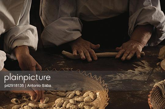 Chefs rolling gnocchi dough in kitchen - p42918135 by Antonio Saba
