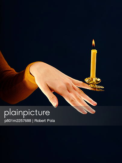 Woman with one candlestick and candle on her finger - p801m2257688 by Robert Pola
