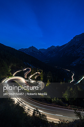 Light trails on the hairpin curves of Maloja Pass mountain road at night, Engadine, Canton of Graubunden, Switzerland, Europe - p871m2152457 by Roberto Moiola
