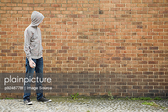 Boy by wall with spray can - p9248778f by Image Source