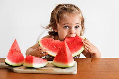 Portrait of cute baby girl eating watermelon while sitting at wooden table against wall in house - p1166m2112698 by Cavan Images
