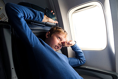 Boy Stretching in Airplane - p1262m1191161 by Maryanne Gobble