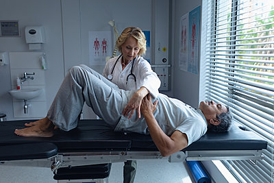 Female doctor examining male patient back in hospital - p1315m2117810 by Wavebreak