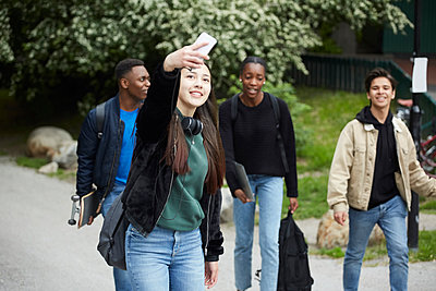 Smiling teenage girl taking selfie while standing against friends walking on street - p426m2135432 by Maskot