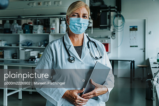 Scientist wearing face mask holding digital tablet while standing at laboratory - p300m2226902 by Mareen Fischinger