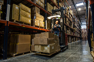 Warehouse worker wearing a safety harness while operating a motorized stock picker in an aisle between large racks of cardboard boxes holding product on pallets in a large distribution warehouse. - p1100m1575493 by Mint Images
