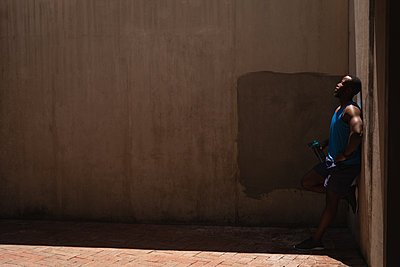 Man standing beside the wall on a sunny day - p1315m2091206 by Wavebreak