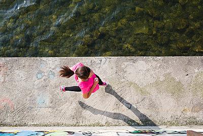 Young woman running at lakeshore - p300m1140761 by Michela Ravasio