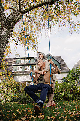 Happy woman embracing senior man on a swing in garden - p300m2156252 by Gustafsson