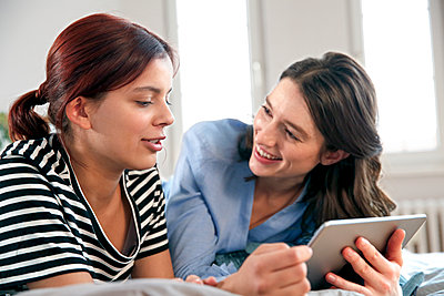 Happy mother and daughter lying on bed at home sharing tablet - p300m2188575 by Florian Küttler